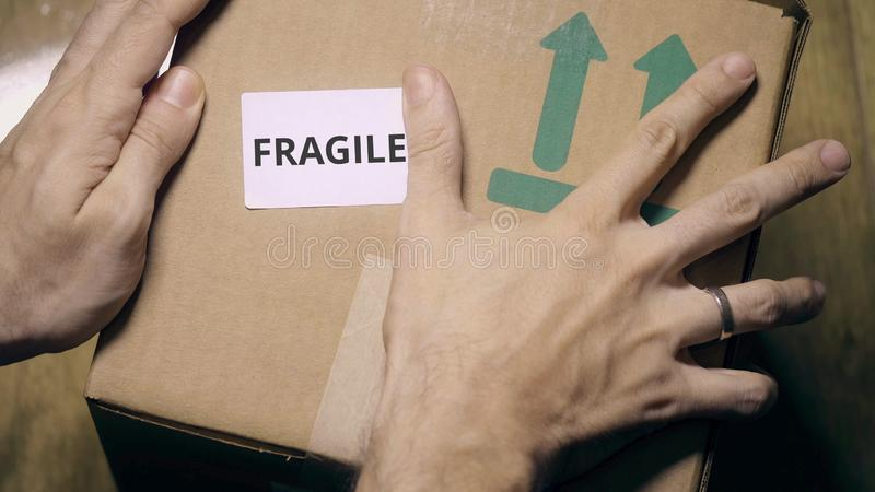 Marking box with FRAGILE label. Labeling carton with a sticker royalty free stock image