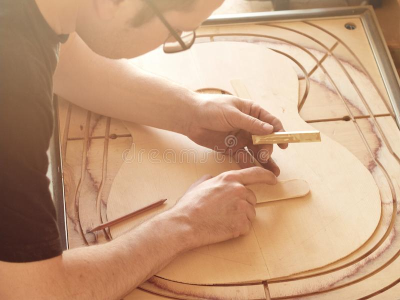 Marking and Pasting of footer and brace to the soundboard of classical guitar. royalty free stock photo