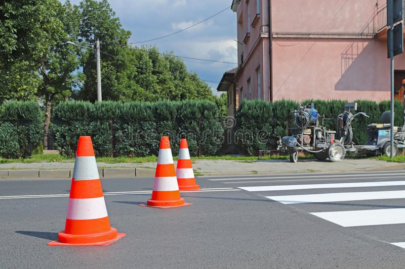Marking with traffic signs a new colored pedestrian crossing. Restriction of traffic by road signs. A machine for drawing and upda. Ting road marking. Safety and stock image