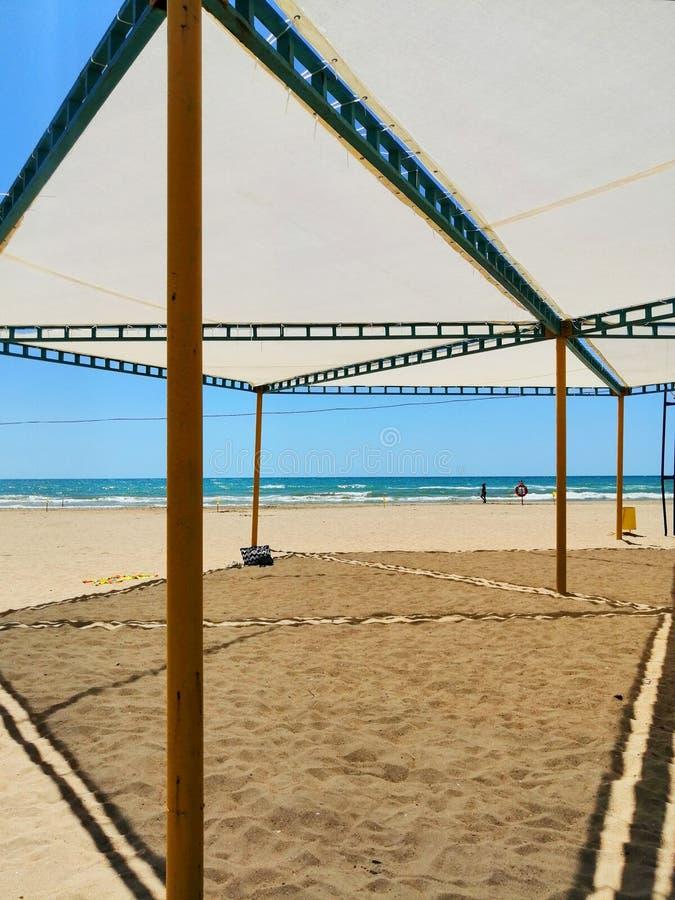 Markis från solen på en sandig strand royaltyfria bilder