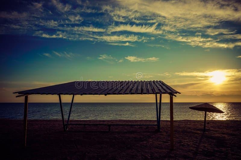 Markis och gammalt metallparaply på en tom sandig strand på solnedgången royaltyfri fotografi