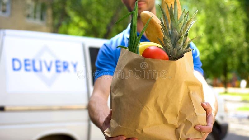 Marknadsföra arbetaren som ger livsmedelsbutikpåsen, godshemsändning, uttrycklig matbeställning royaltyfria bilder
