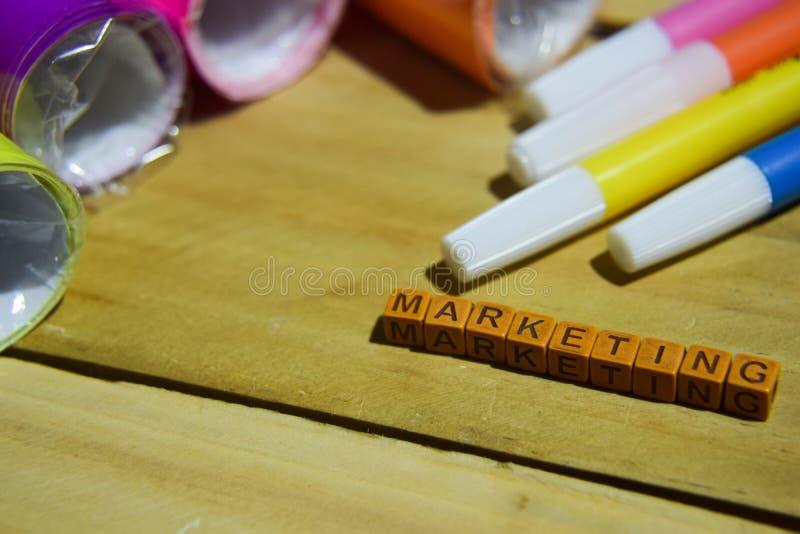 Marknadsföra på träkuber med färgrikt papper och pennan, begreppsinspiration på träbakgrund arkivbilder