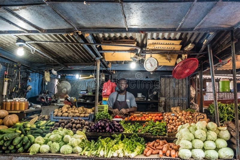 Marknadsföra ställningen, mannen som in säljer frukter och grönsaken på matmarknad royaltyfri fotografi