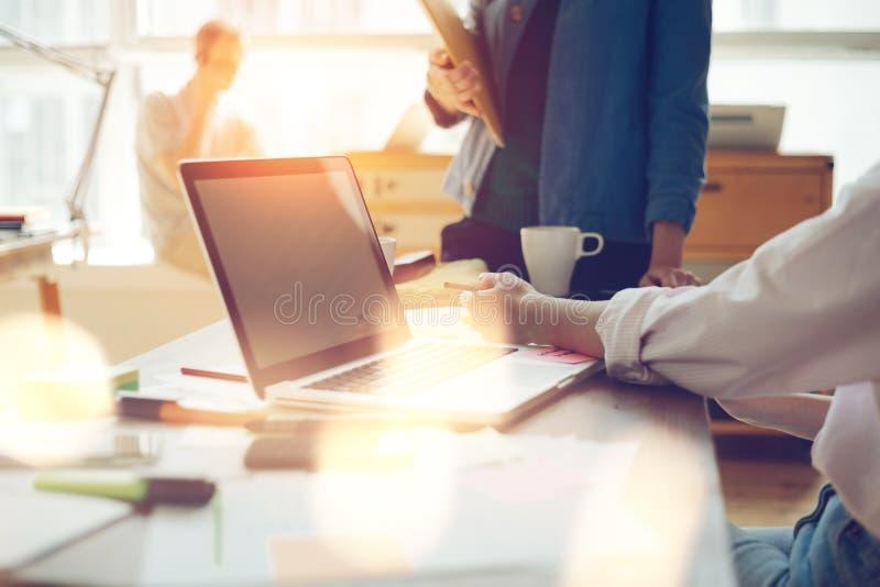 Marknadsföringslag som diskuterar den nya arbetsritningen Bärbar dator och skrivbordsarbete i öppet utrymmekontor royaltyfri fotografi