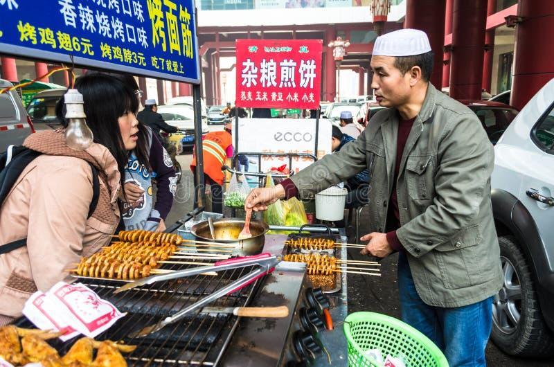 Marknadsförsäljare på gatan av Xian erbjuder deras kunder som nationell mat från deras gatamat stannar, det Shaanxi landskapet, K royaltyfri foto