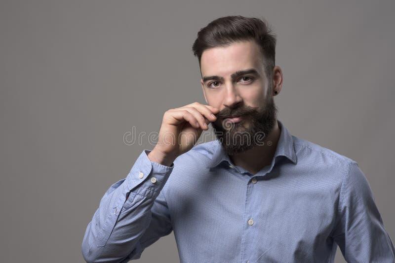 Markotny portret młodego eleganckiego brodatego mężczyzna twirling wąsy i patrzeć kamerę zdjęcia stock