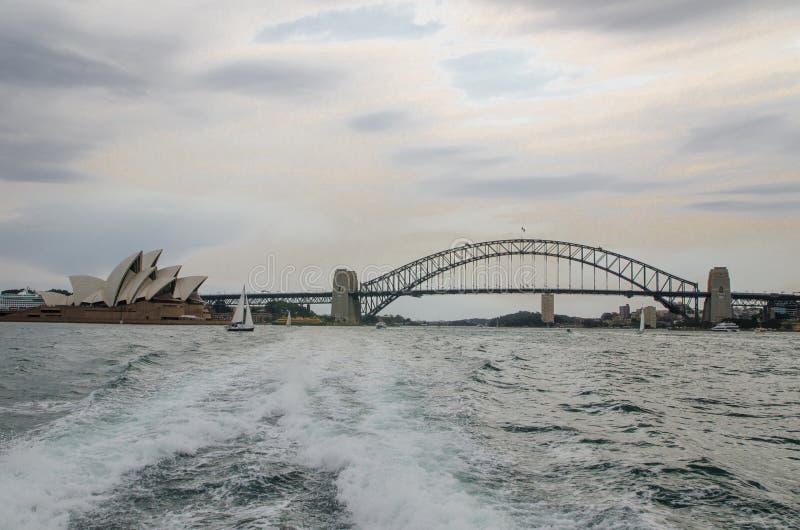 Marksteinstadtbild von Sydney-Opernhaus und von Hafenbrücke, das Bild wurde von der Rückseite der Fähre am Tag des bewölkten Himm stockfotografie