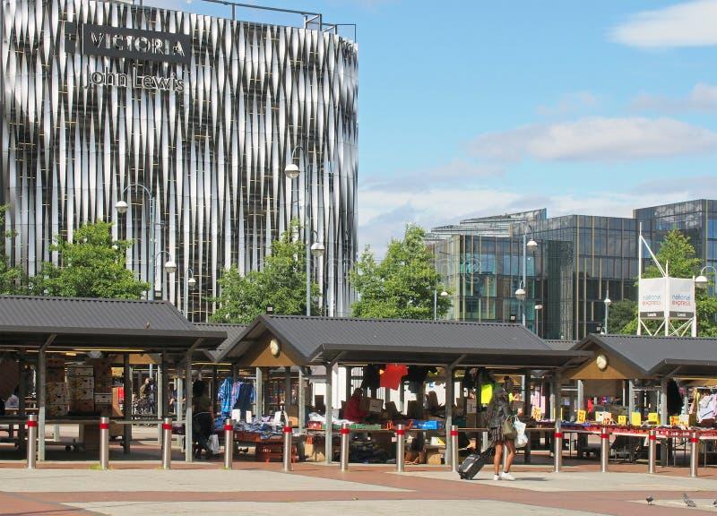 Markt Leeds im Freien mit den Leuten, die an den traditionellen Ställen verkaufen Kleidung und Nahrung vor dem modernen Victoria- lizenzfreie stockfotografie