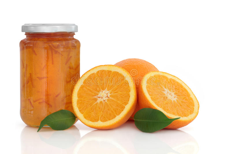 Marmalade Jam. In a jar with orange fruit whole and in halves with leaf sprigs, over white background royalty free stock images