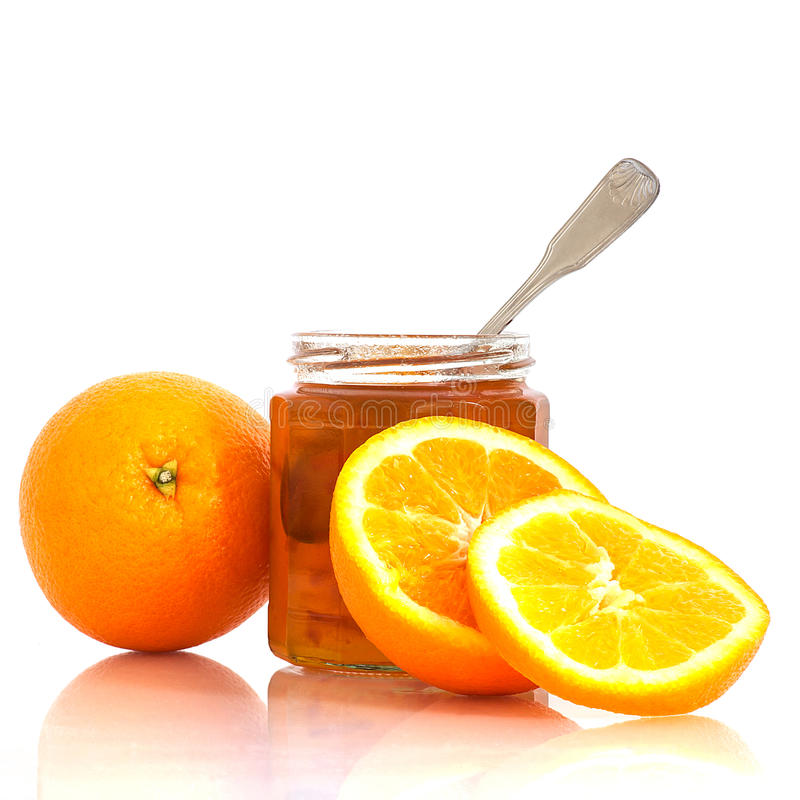 Marmalade in jar and oranges. Closeup of orange slices and orange marmalade in a jar, isolated on white background royalty free stock photos