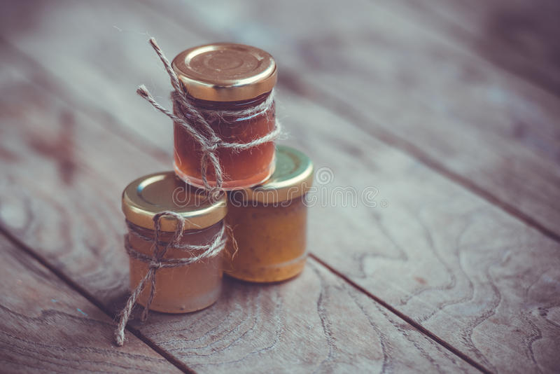 Marmalade. Three small jars of marmalade or jam on wooden table. Toned image stock images