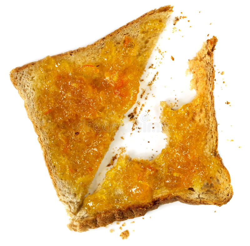 Marmalade Toast. Toast with orange marmalade. Overhead view, with bites missing, isolated on white royalty free stock photography