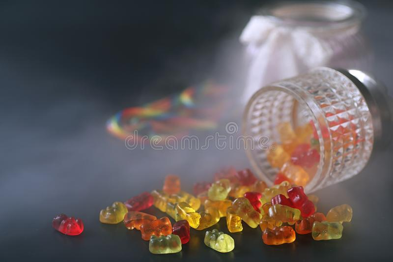 Marmalade in a vase on the table. Sweets in a bowl on a black ba stock image