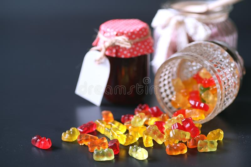 Marmalade in a vase on the table. Sweets in a bowl on a black ba stock images