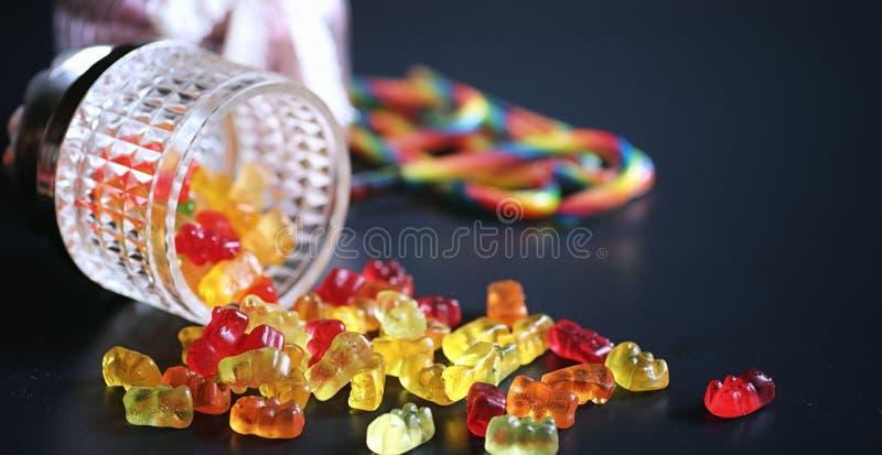 Marmelade in een vaas op de lijst Snoepjes in een kom op zwarte bedelaars royalty-vrije stock afbeeldingen