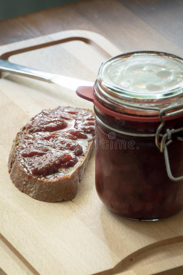 Homemade jam with bread and a knife stock photography