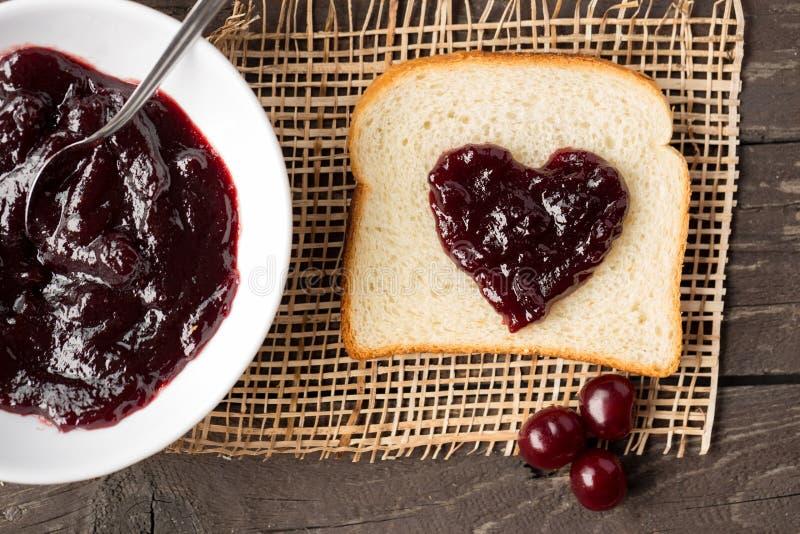 Marmellata di amarene e pane tostato con cuore fotografia stock