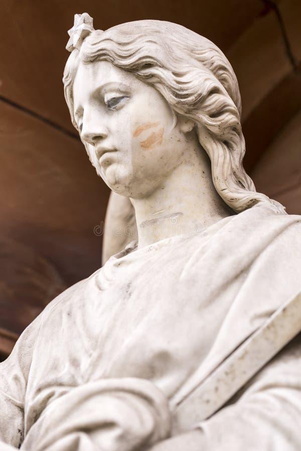 Marmeren beeldhouwwerk met lippenstiftkus op haar wang stock foto