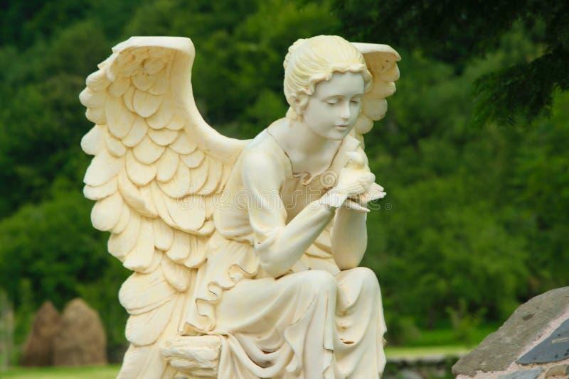 Marmeren beeldhouwwerk van vrouwelijke engelenzitting op de rots en holding een vogel in haar handen royalty-vrije stock afbeeldingen
