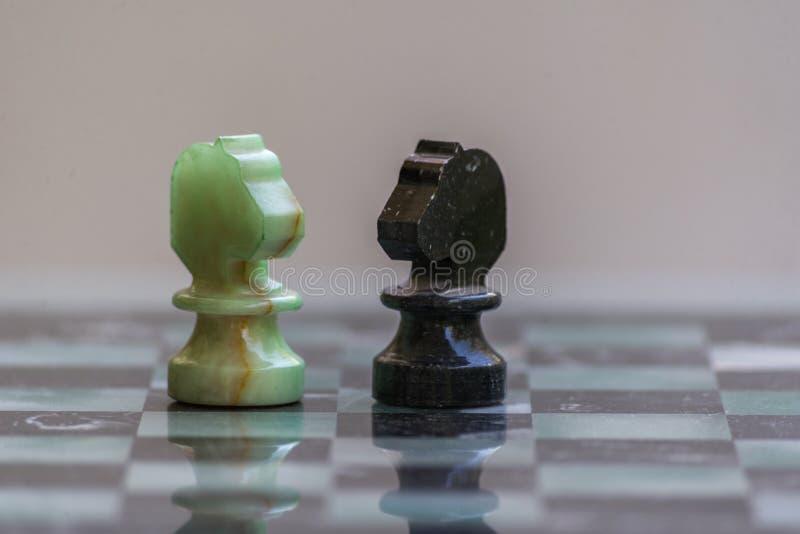 Marmeren schaakstukken, op een marmeren schaakbord close-up stock fotografie