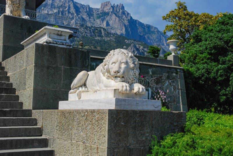 Marmeren standbeeld van een leeuw tegen een achtergrond van bergen, vegetatie en blauwe hemel royalty-vrije stock foto's