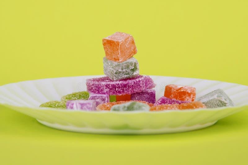 Marmoladowy i zachwycie na żółtym tle Tureccy cukierki Barwi?cy marmoladowy S?odka owocowa cytryna marmoladowa Galaretowi cukierk fotografia stock