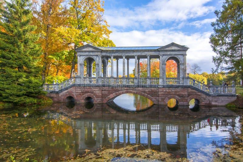 Marmorbron i guld- nedgång i Catherine parkerar, Tsarskoe Selo, St Petersburg, Ryssland royaltyfri fotografi