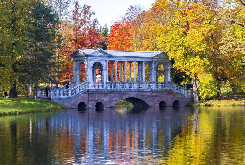 Marmorbron i höstlövverk i Catherine parkerar Pushkin, St Petersburg, Ryssland fotografering för bildbyråer