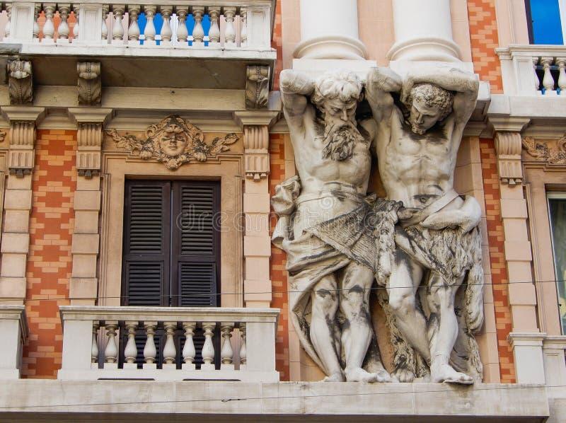 Marmorera dekorativa statyer på fasaden av en historisk byggnad i mitten av Genoa Genova, Italien arkivbild