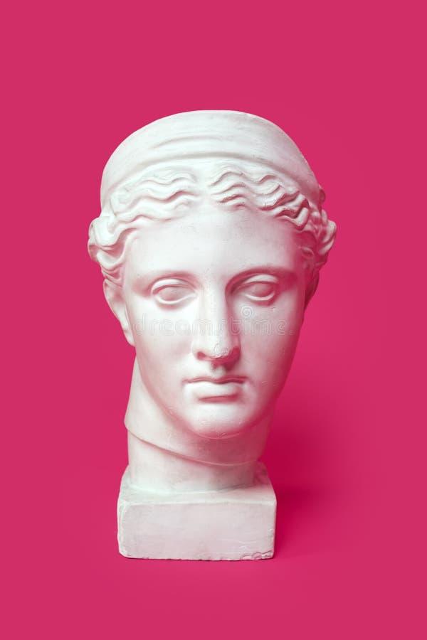 Marmorera huvudet av den unga kvinnan, gammalgrekiskagudinnabysten som isoleras på rosa bakgrund royaltyfri fotografi