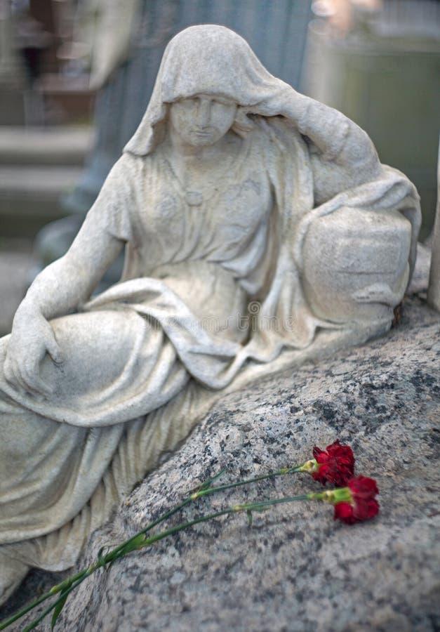 Marmorera skulptur av en sörja kvinna över en grav in med två royaltyfri bild