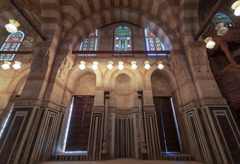 Marmorera väggen med mihraben inbäddade nischen, trädörrar, enorma bågar och målat glassfönster, Khayer Bek Mausoleum, Kairo, Egy royaltyfria foton