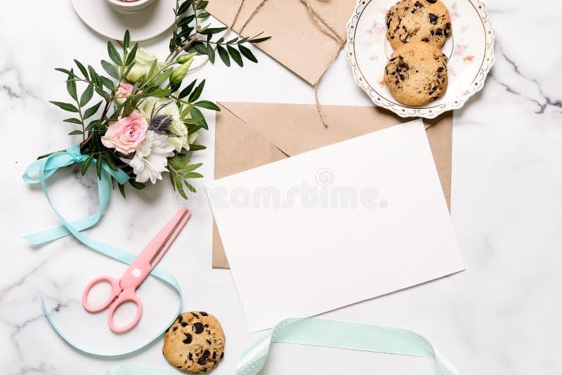 Marmorschreibtisch mit Blumenstrauß von Blumen, rosa Scheren, Postkarte, Kraftpapier-Umschlag, Baumwollniederlassung, Haferplätzc lizenzfreie stockfotografie