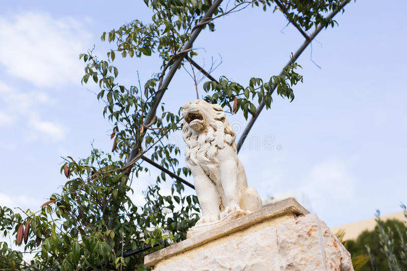 Marmorskulptur av ett lejon på sockel arkivfoto