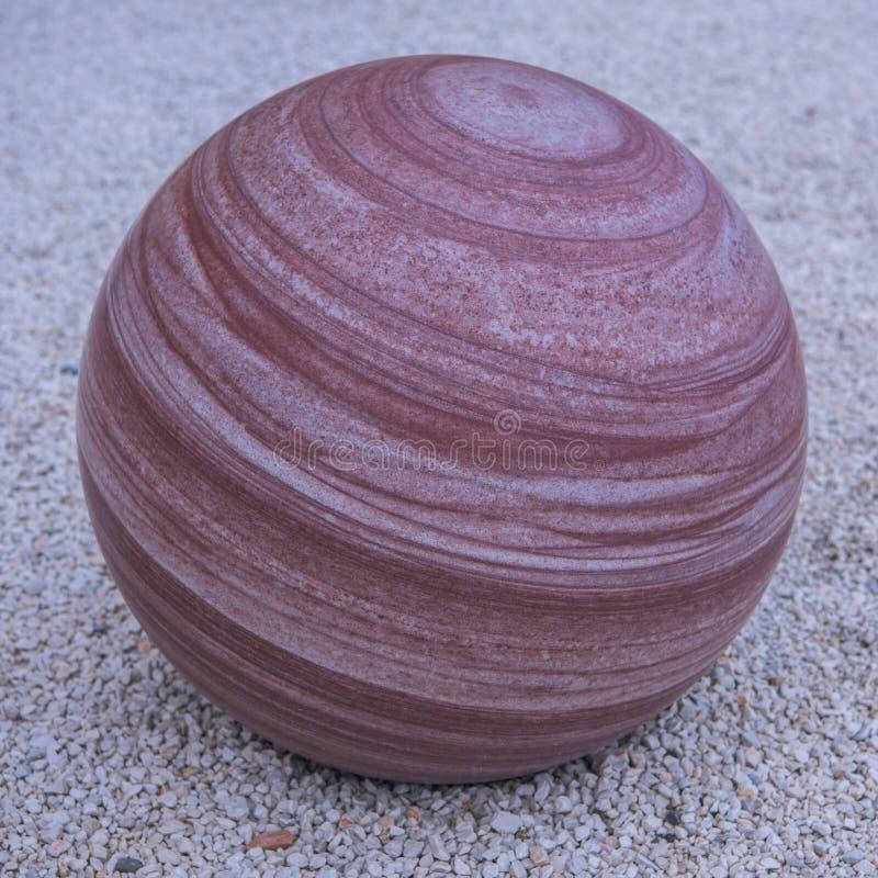Marmurkowaty kamienny sfery round paskujący w czerwieni zdjęcia royalty free