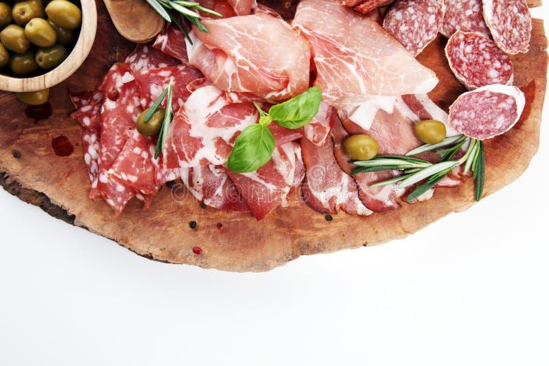 Marmurowa tnąca deska z prosciutto, bekonem, salami i kiełbasami na drewnianym tle, Mięsny półmisek obrazy stock