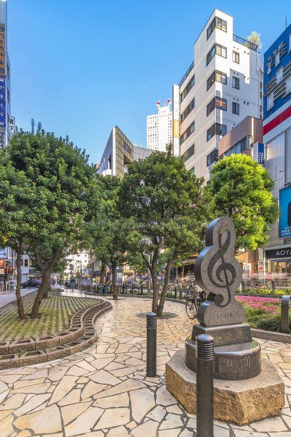 Marmurowy zabytek kształtujący w treble clef na światło słoneczne ulicie przy wschodnim wyjściem Ikebukuro w Tokio Chodniczek krz fotografia royalty free