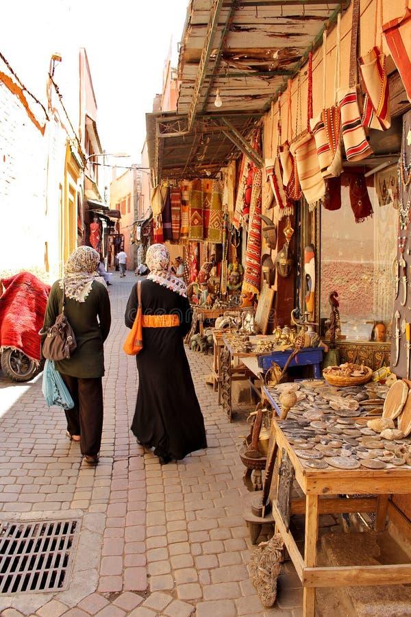 Marockanska kvinnor i de färgrika gatorna av den huvudsakliga souken av Marrakesh royaltyfria foton