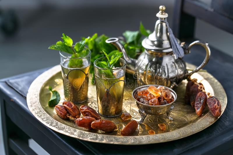 Marokańska mn herbata w tradycyjnych szkłach z mennicą, datami i cukierem, fotografia royalty free