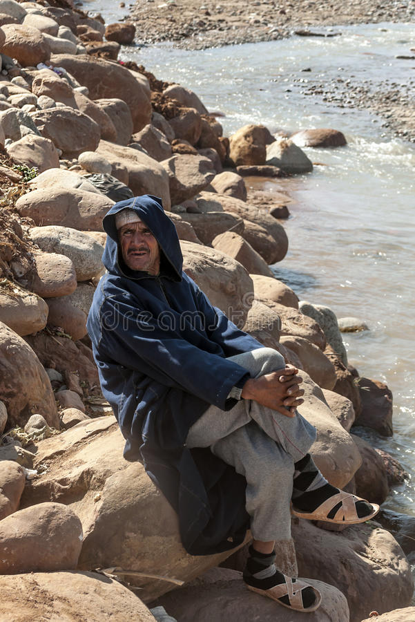 Marokkaanse mensenzitting op de bank van een rivier royalty-vrije stock afbeelding