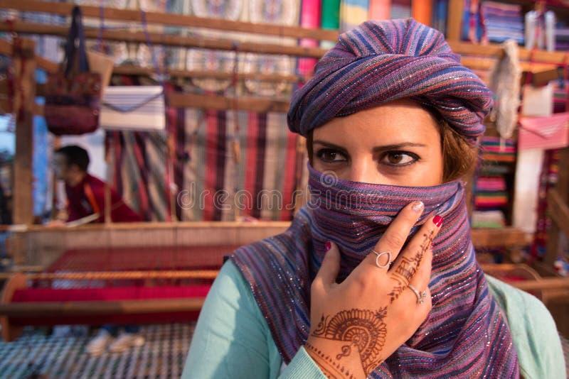 Marokkaanse vrouw met zijdesjaal die haar gezicht in Marokko behandelt met weefgetouwen op de achtergrond stock fotografie
