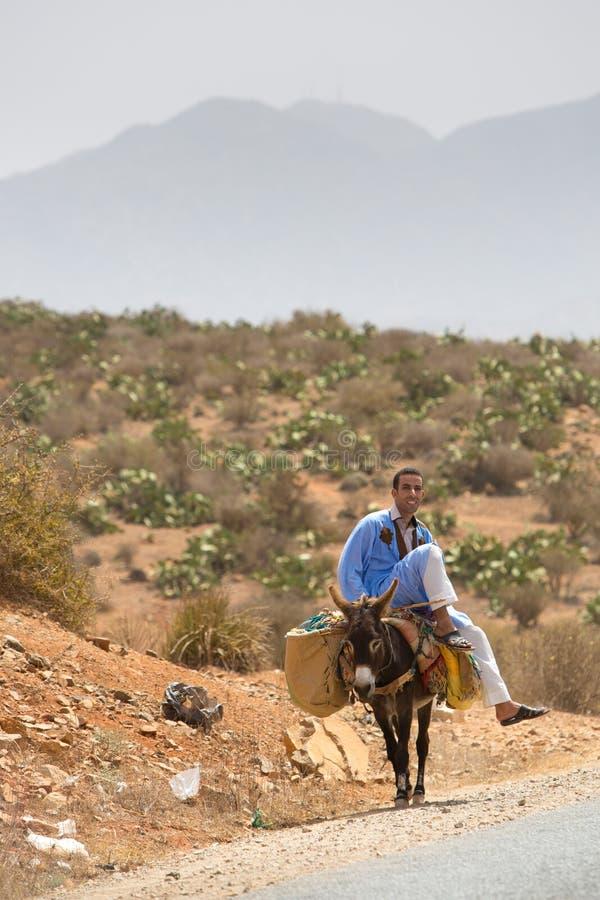 Marokkanischer Mann, der auf seinem Esel, Marokko sitzt lizenzfreie stockbilder