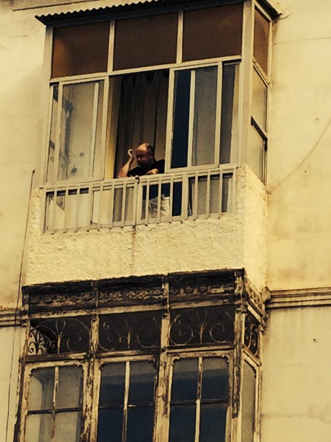 Marokko-Mann auf Balkon des Altbaus stockfotos
