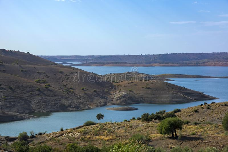 Maroko, lake water reservoir in the Atlas Mountains seen from a high point of view, with deep blue water, and tall bald striped. Maroko, lake water reservoir in royalty free stock images