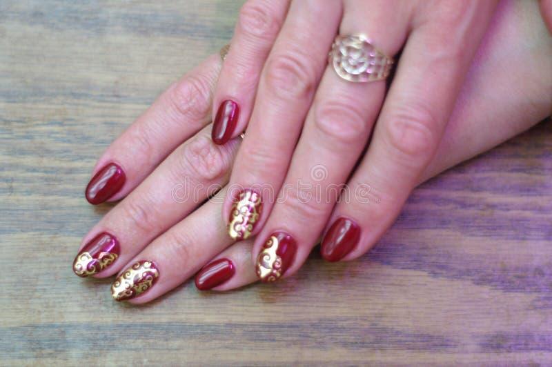 Maroon ногти с золотой металлической картиной стоковые фотографии rf