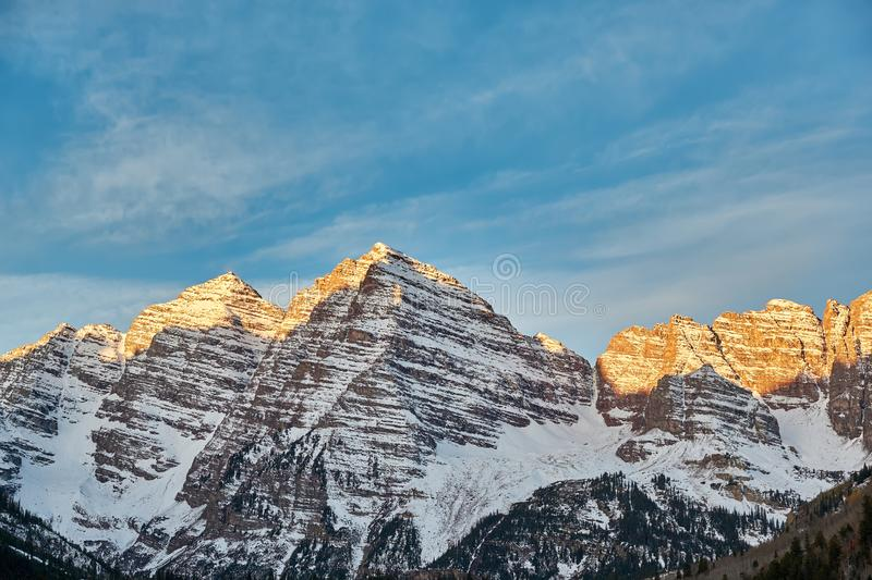 Maroon Bells mountains in snow at sunrise stock photo