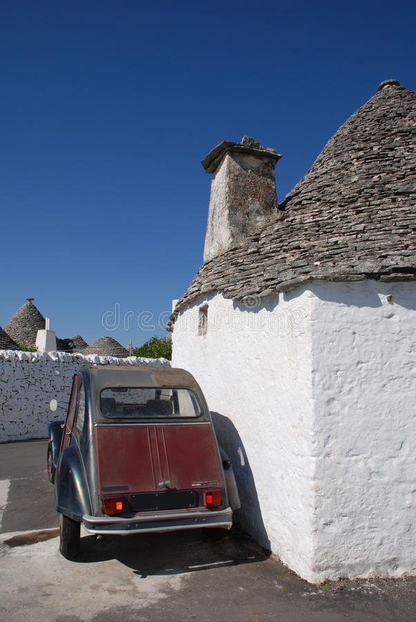 Maroon Car Outside Trullo. An old maroon car parked outside one of the trullo houses of Alberobello, Italy. The trulli, which are protected under UNESCO World stock photos