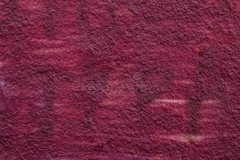 The maroon dilapidated cement wall texture. Dark pink stucco background. Abstract pattern of grunge red concrete wall. Vinous pain royalty free stock photos