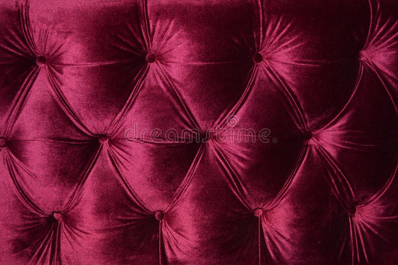 Maroon velor sofa upholstery beautiful. Close up stock photos